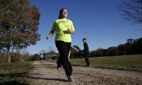 A girl jogging at a park.